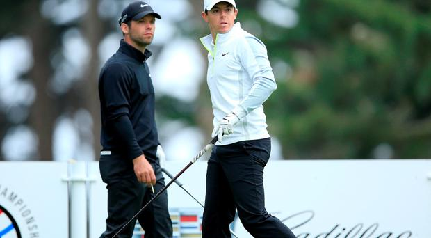 Rory McIlroy of Northern Ireland follows his tee shot at the par 4, 11th hole as his opponent Paul Casey of England looks on during his quarter final match in the World Golf Championships Cadillac Match Play at TPC Harding Park