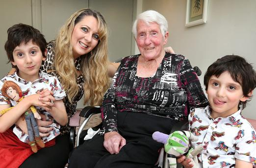 Twins Hassan (left) and Hussein Benhaffaf (5), with their mum Angie, meet Oonagh O'Neill from Dalkey at the Dalkey Lodge Nursing Home for the first time. Photo: Steve Humphreys