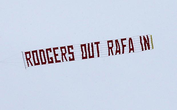 A plane flies a banner displaying 'Rodgers Out Rafa In' before the Barclays Premier League match at Anfield