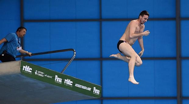 An intruder jumps into the pool during the Men's 10m Final during the FINA/NVC Diving World Series at the Aquatics Centre in London Photo: Michael Regan/Getty Images