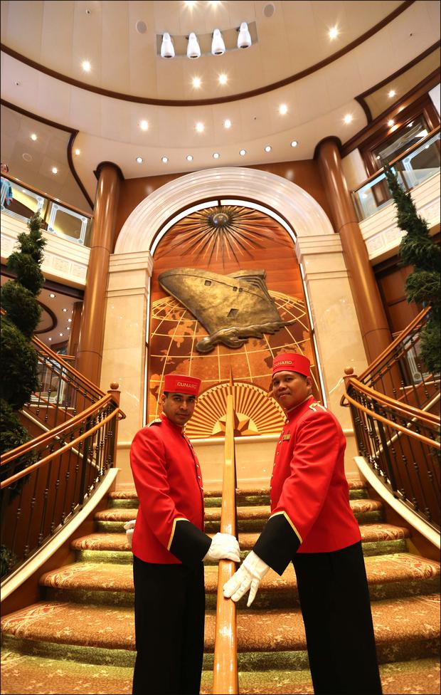 Cunard 175th anniversary celebrations, Queen Victoria cruise to commemorate the 100th anniversary of the sinking of Lusitania.Bell boys in the grand atrium of the Queen Victoria. Sunday 3rd May 2015 Picture credit: Paul Collins