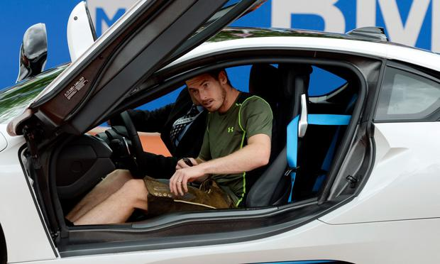 Andy Murray, dressed in a 'Lederhose', Bavarian leather trousers, sits in the car he was presented with during the award ceremony following his final match against Germany's Philipp Kohlschreiber during the ATP Tennis BMW Open in Munich,