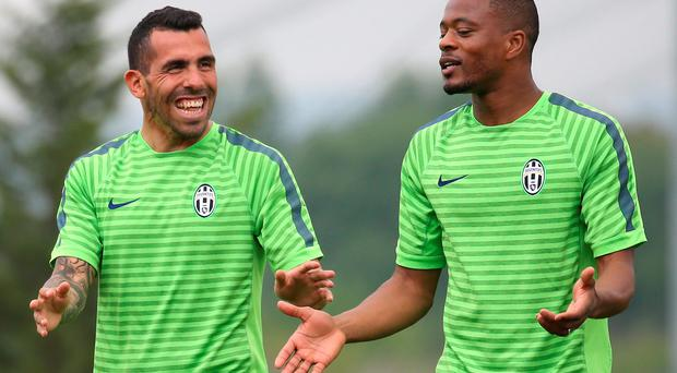 Carlos Tevez shares a joke with Patrice Evra during Juventus training ahead of the clash against Real Madrid