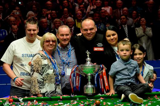 Stuart Bingham celebrates with his family and the trophy after winning the Betfred World Championships at the Crucible