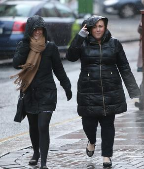 Two ladies shelter from the rain in Dublin city centre