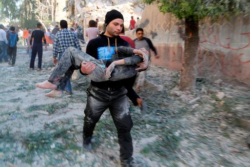A man holds an injured boy after what activists said was a barrel bomb dropped by forces loyal to Syria's President Bashar al-Assad Credit: Hosam Katan