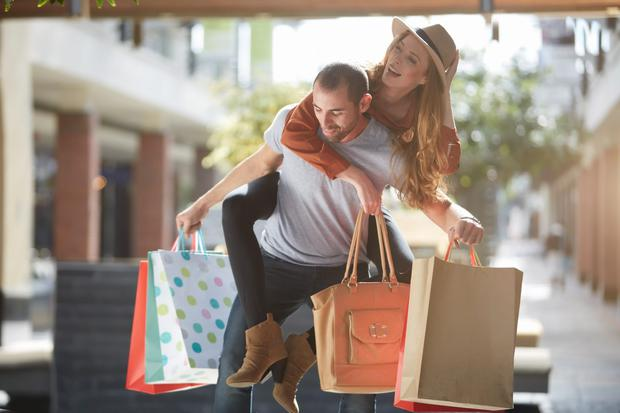 Man carrying woman on back, holding shopping bags
