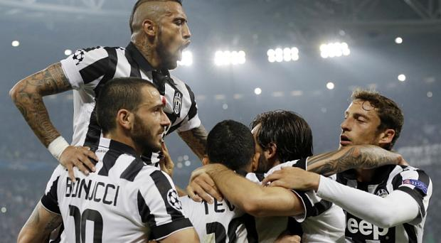 Juventus' Carlos Tevez celebrates with his teammates, from left, Arturo Vidal, top, Leonardo Bonucci, Andrea Pirlo and Claudio Marchisio after scoring during the Champions League, semi-final against Real Madrid