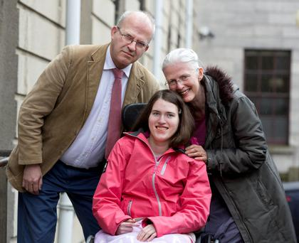 Emily Casey, of Dalkey, Dublin with her parents, Stephani and Dermot outside the Four Courts after the High Court approved a €1.6m interim payment following a High Court action. Pic: Collins Courts
