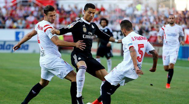Real Madrid's Cristiano Ronaldo (C) is challenged by Sevilla's Grzegorz Krychowiak (L) and Diogo Gomes Figueiras during their Spanish first division soccer match at Ramon Sanchez Pizjuan stadium in Seville, southern Spain