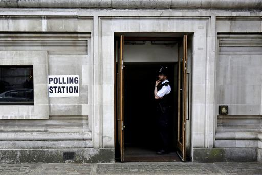 A policeman looks out from a polling station near the Houses of Parliament in London. Reuters/Kevin Coombs