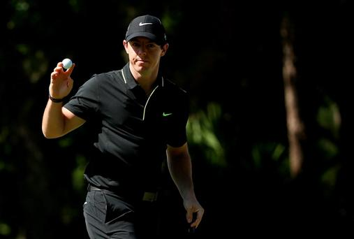 Rory McIlroy holds up his ball after putting for birdie on the 15th green