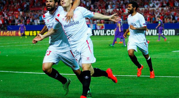 Kevin Gameiro of Sevilla celebrates scoring his team's third goal with team mate Coke during the UEFA Europa League Semi Final first leg match between FC Sevilla and ACF Fiorentina at Estadio Ramon Sanchez Pizjuan