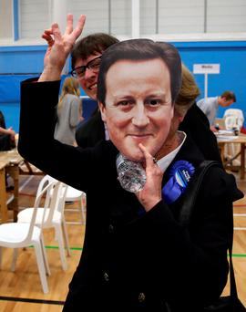 A Conservative team member wears a David Cameron mask in Coleshill Leisure Centre in Coleshill during the General Election 2015 count. Photo: Simon Cooper/PA Wire