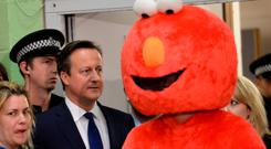 Prime Minister David Cameron (left) walks past a candidate man dressed as Elmo during the General Election count at the Windrush Leisure Centre in Witney. PRESS ASSOCIATION Photo. Picture date: Friday May 8, 2015. Photo credit should read: Stefan Rousseau/PA Wire
