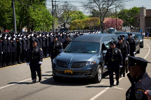 Police officers line the streets as a hearse carrying the body of slain NYPD officer Brian Moore passes Credit: Mike Segar
