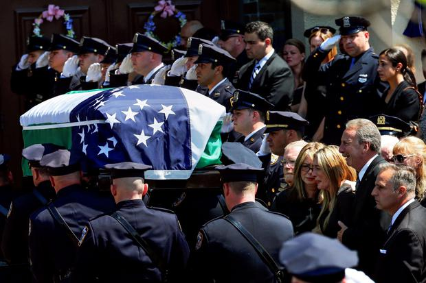 Parents Raymond (bottom row, 3rd R) and Irene (bottom row, 5th R), and sister Christine (bottom row, 4th R) of NYPD officer Brian Moore Credit: Shannon Stapleton