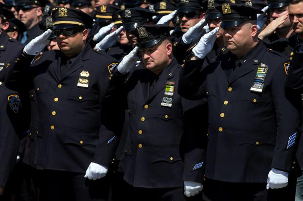NYPD officers salute as thousands of officers stand at attention Credit: Mike Segar
