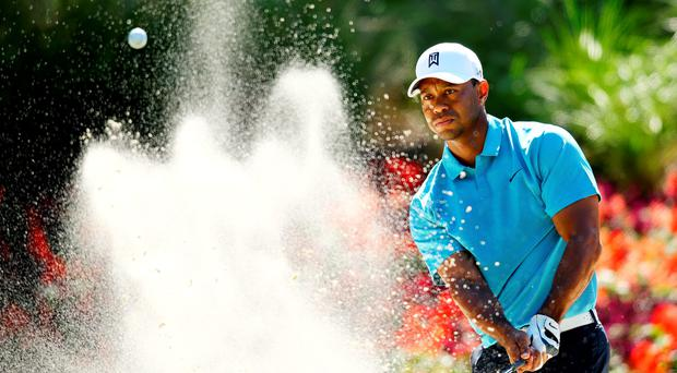 Tiger Woods plays his shot from a bunker to the 14th green during the second round of The Players Championship at Sawgrass