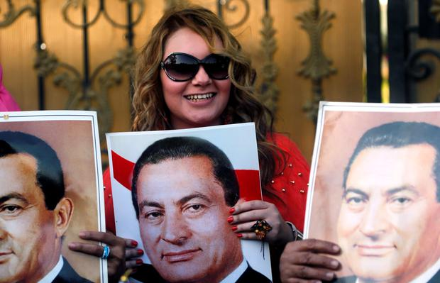 A supporter of ousted Egyptian president Hosni Mubarak cheers with a picture of him Credit: Amr Abdallah Dalsh