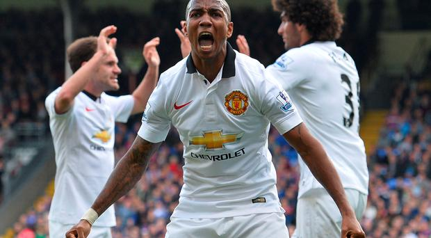 Manchester United's English midfielder Ashley Young (front) celebrates after Manchester United's Belgian midfielder Marouane Fellaini (back R) scored his team's second goal