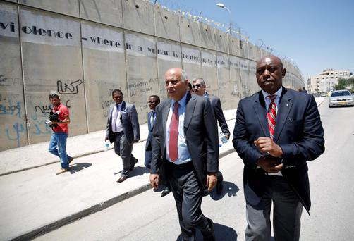 Head of the Palestinian Football Association Jibril Rajoub walks with anti-apartheid activist Tokyo Sexwale (R) past Israel's controversial barrier Credit: Mohamad Torokman