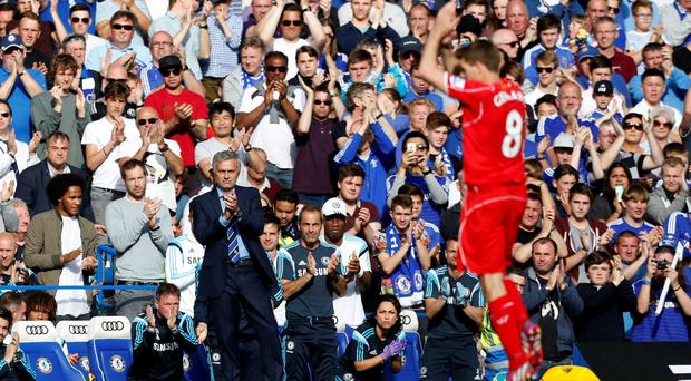 Chelsea's Portuguese manager Jose Mourinho (L) leads the applause after Liverpool's English midfielder Steven Gerrard (R) is substituted