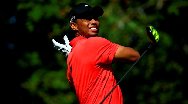 Tiger Woods drops his driver as he plays his shot from the seventh tee