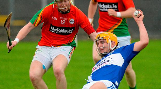 Charles Dwyer of Laois loses his footing while under pressure from Carlow's Paul Coady