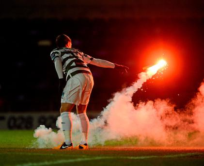 Shamrock Rovers player Thomas Stewart tosses away a flare during their 2013 Setanta Cup clash with Linfield in Windsor Park