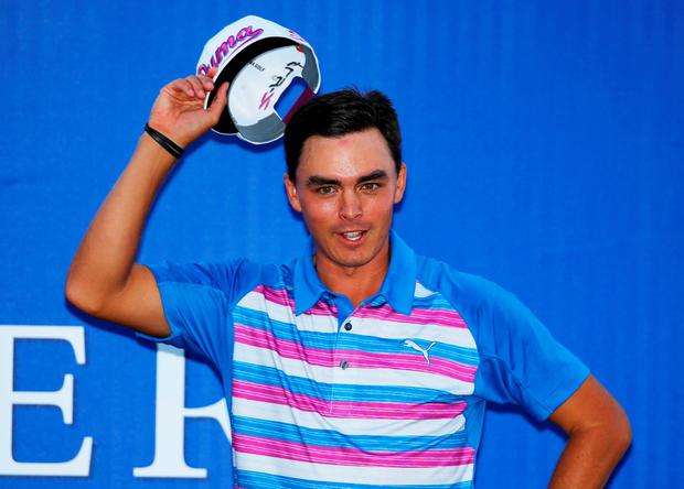 Rickie Fowler celebrates with the winner's trophy after the final round of The Players Championship at the TPC Sawgrass