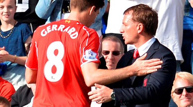 Liverpool's Northern Irish manager Brendan Rodgers (R) has a word with Liverpool's English midfielder Steven Gerrard (L) as he is substituted during the English Premier League football match between Chelsea and Liverpool at Stamford Bridge in London on May 10, 2015. AFP PHOTO / GLYN KIRK RESTRICTED TO EDITORIAL USE. No use with unauthorized audio, video, data, fixture lists, club/league logos or live services. Online in-match use limited to 45 images, no video emulation. No use in betting, games or single club/league/player publications.GLYN KIRK/AFP/Getty Images