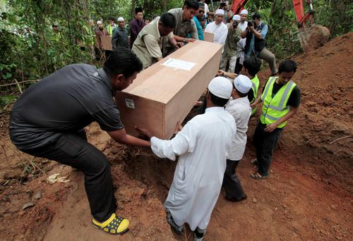 Thai Muslim villagers and rescue workers carry a coffin, which contains the remains of Rohingya migrants, for burial after a funeral at a graveyard in Thailand's southern Songkhla province May 10, 2015. REUTERS/Surapan Boonthanom