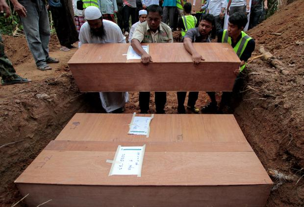Thai Muslim villagers and rescue workers place coffins, which contain the remains of Rohingya migrants, into a grave for burial after a funeral ceremony at a graveyard in Thailand's southern Songkhla province May 10, 2015. REUTERS/Surapan Boonthanom