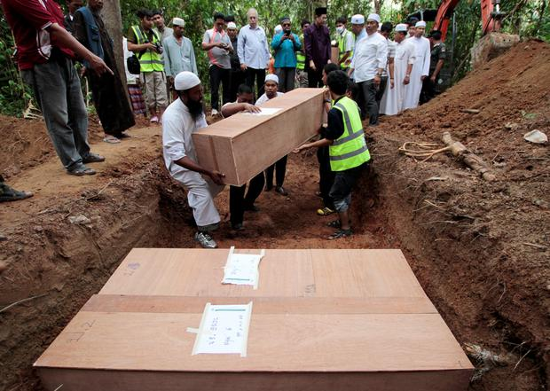 Thai Muslim villagers and rescue workers place coffins, which contain the remains of Rohingya migrants, into a grave for burial after a funeral at a graveyard in Thailand's southern Songkhla province May 10, 2015. REUTERS/Surapan Boonthanom