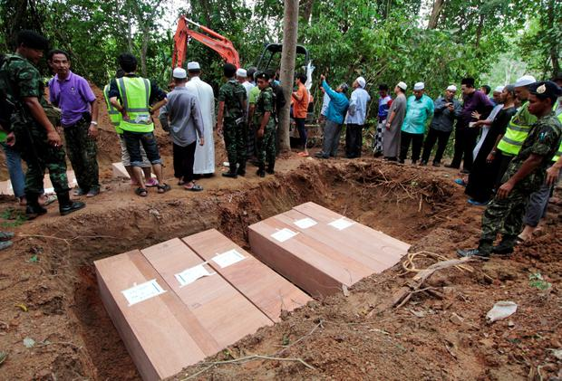 Thai Muslim villagers and security forces watch as coffins containing the remains of Rohingya migrants are placed in a grave for burial after a funeral at a graveyard in Thailand's southern Songkhla province May 10, 2015. REUTERS/Surapan Boonthanom