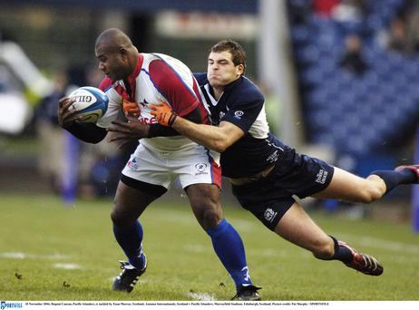 Rupeni Caucau, Pacific Islanders, is tackled by Euan Murray, Scotland