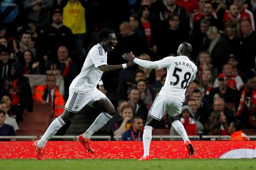 Swansea City's French striker Bafetimbi Gomis (L) celebrates scoring his goal with Swansea City's Gambian-Swedish striker Modou Barrow