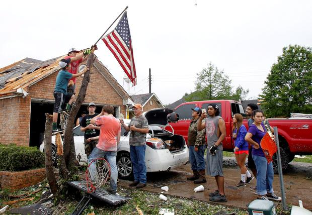 Aldyn Roan and David Arce (top) mount an American flag to a broken tree trunk in front of the Arce home after a tornado swept through the area the previous night in Van, Texas