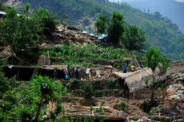 Medical team members of Medecins Sans Frontieres walk past damaged homes in the village of Ebi in Dhading district some 60kms north-west of Kathmandu on May 11, 2015. The April 25, 2015 disaster completely destroyed 288,798 houses nationwide in Nepal while 254,112 homes were partially damaged, according to the Himalayan country's National Emergency Operation Centre. Large areas of Kathmandu were turned into piles of rubble and almost two weeks on from the 7.8-magnitude quake thousands are still living in makeshift tents in the capital. AFP PHOTO / PRAKASH MATHEMAPRAKASH MATHEMA/AFP/Getty Images
