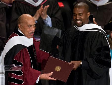 Musician Kanye West (R) receives an honorary doctorate degree from School of the Art Institute of Chicago President Walter Massey during their annual commencement ceremony in Chicago, Illinois, May 11, 2015. And he smiles...