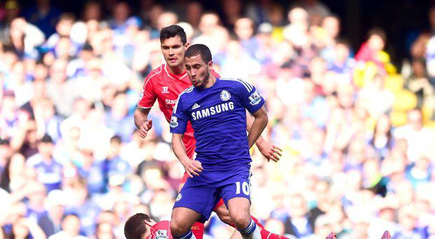 Chelsea's Eden Hazard gets the better of Liverpool's Steven Gerrard (floor) as they battle for the ball during the Barclays Premier League match at Stamford Bridge