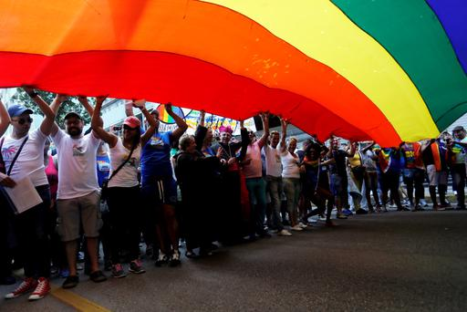 Gay rights activists lift a rainbow flag during the Eighth Annual March against Homophobia and Transphobia in Havana, May 9, 2015. Reuters/Stringer