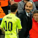 Barcelona's Lionel Messi (L) shakes hands with his former coach Pep Guardiola as he leaves the pitch at half time during the UEFA Champions League football match semi final FC Bayern Munich vs FC Barcelona in Munich