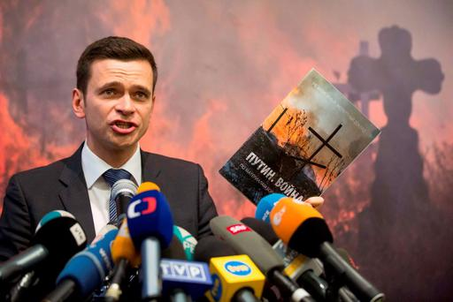 Russian opposition figure Ilya Yashin holding a report by slain Russian opposition leader Boris Nemtsov. Photo: AP