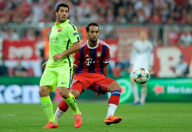 Bayern Munich's Medhi Benatia and Barcelona striker Luis Suarez vie for the ball