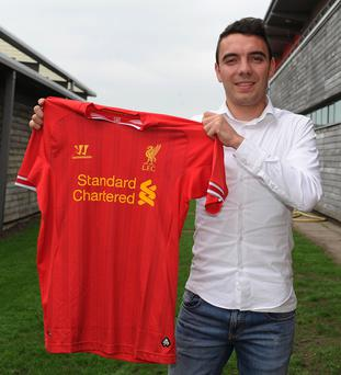 Iago Aspas poses with the team shirt after signing for Liverpool FC