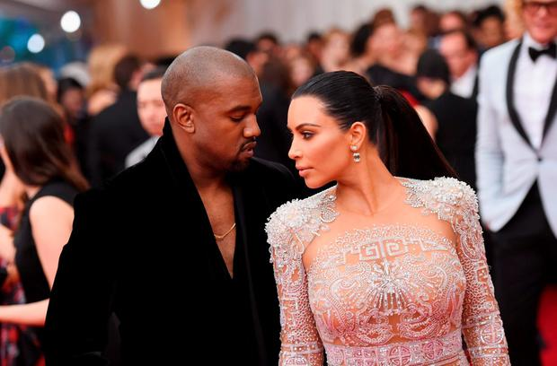 Kanye West (L) and Kim Kardashian attend the
