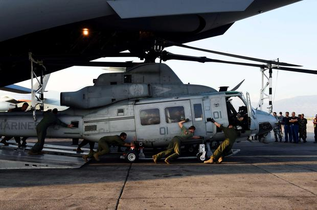 The crew of a US C-17 military transport plane unload a Huey helicopter at Tribhuvan International Airport in Kathmandu Credit: Roberto Schmidt (AFP)