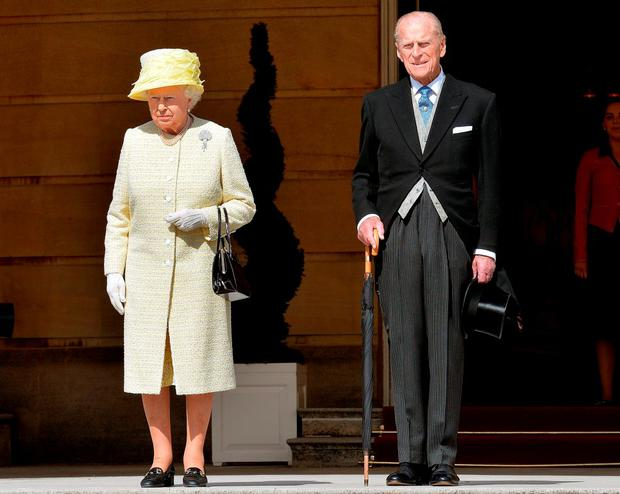 Britain's Queen Elizabeth II (L) and Prince Philip, Duke of Edinburgh stand for the national anthem at a garden party held at Buckingham Palace
